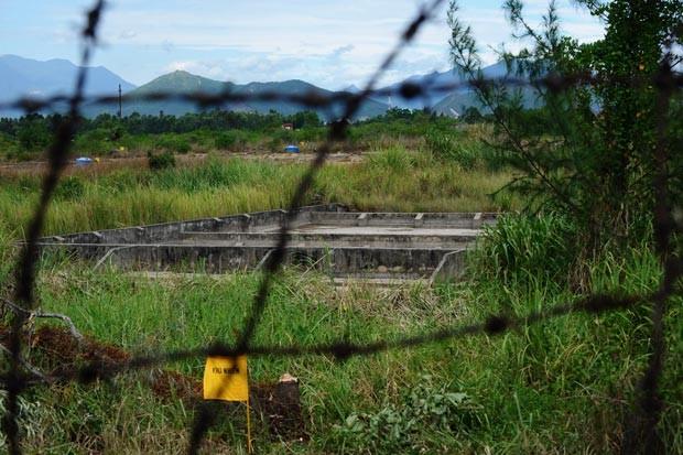 Área contaminada é marcada com bandeira amarela perto de aeroporto de Danang, no Vietnã (Foto: Hoang Dinh Nam / AFP)