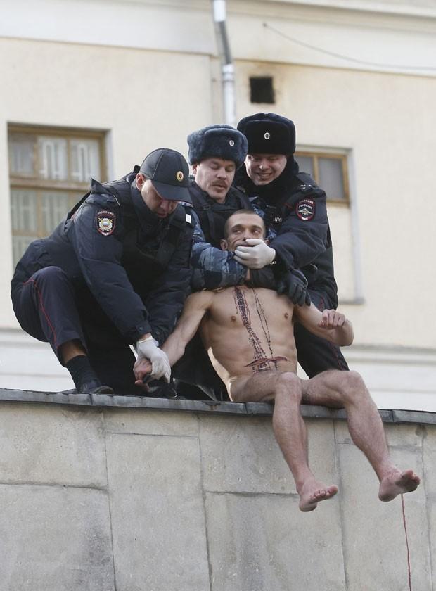 O sangue já havia escorrido por seu corpo quando Pavlensky foi removido por seguranças (Foto: Maxim Zmeyev/Reuters)