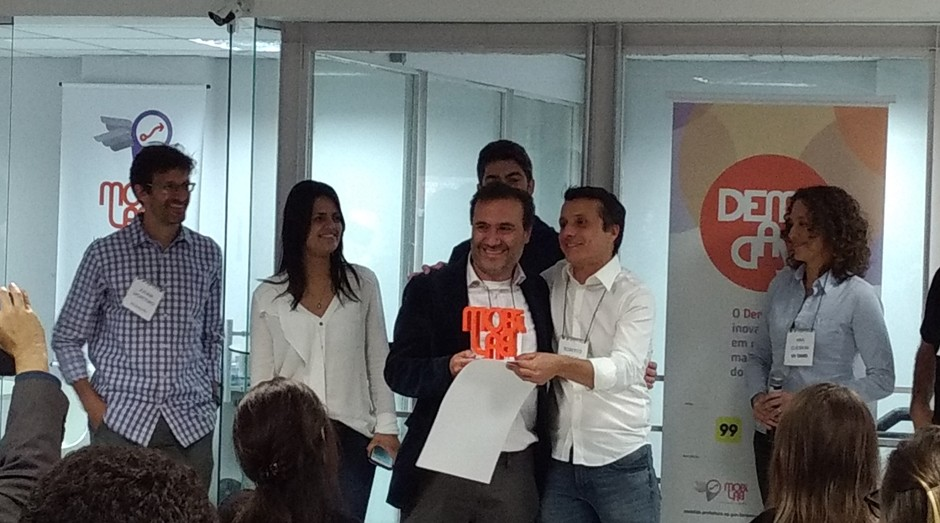 O CEO da Scipopulis, Roberto Speicys, recebe o troféu do MobiLab do professor FGV-SP e coordenador do MobiLab, Ciro Biderman  (Foto: Vitória Batistoti)