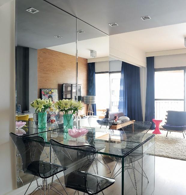 A continuidade gerada pelo espelho e pela mesa de vidro deixa o ambiente mais fluido. As cadeiras de acrílico seguem o estilo moderno da decoração (Foto: Marcelo Magnani)