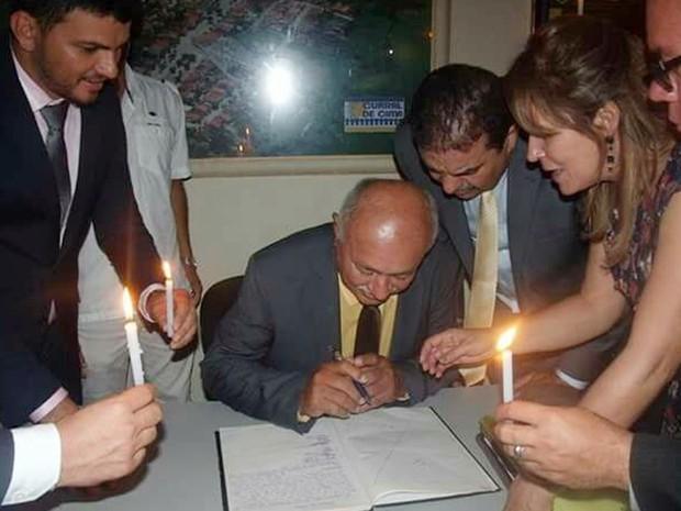 Vice-prefeito de Curral de Cima também precisou das velas para assinar o documento de posse (Foto: Totó Ribeiro/Arquivo Pessoal)