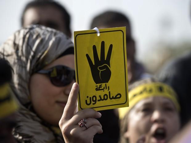 """Apoiadora de Morsi mostra símbolo conhecido como """"Rabaa"""", que significa que quatro em árabe, lembrando os mortos na repressão de acampamento no Cairo. (Foto: Khaled Desouki / AFP)"""