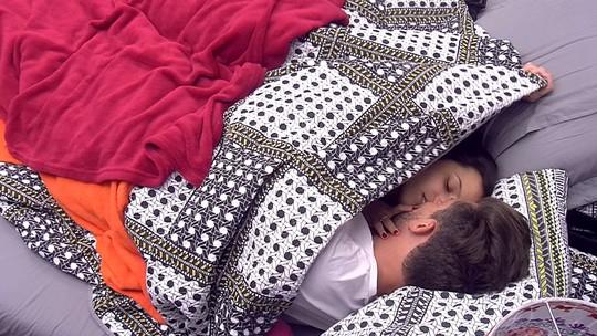 Emilly e Marcos se beijam e se cobrem com o edredom