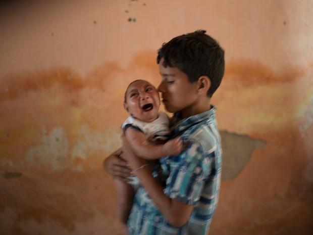 Foto de 23 de dezembro mostra menino Elison, de 10 anos, cuidando de seu irmão de 2 meses José Wesley, que nasceu com microcefalia, em Poço Fundo, no Pernambuco  (Foto: AP Photo/Felipe Dana)