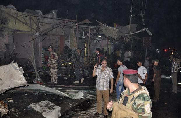Guardas iraquianos vasculham o local de um dos ataques com carro-bomba, em Nasiriyah, a 375 km de Bagdá. Ataques ocorreram também em locais fora da capital (Foto: Reuters/Stringer)