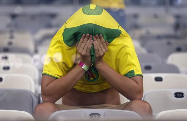 Torcedor cobre o rosto após derrota histórica da Seleção Brasileira. Nunca o Brasil tinha tomado sete gols em uma partida de Copa do Mundo (Foto: Frank Augstein/AP)
