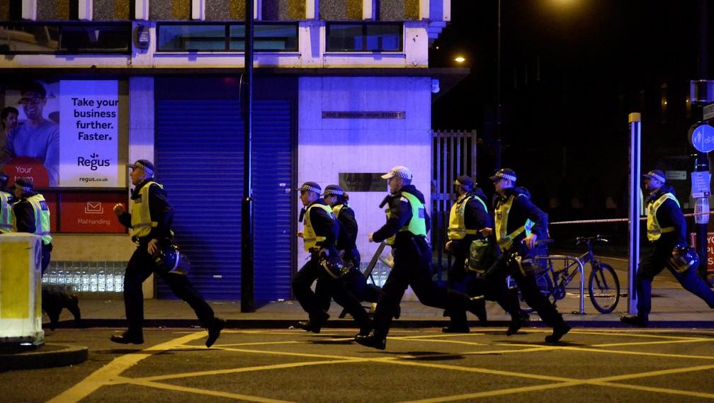 Policiais correm para atender chamado na região da London Bridge (Foto: Reuters / Hannah McKay)
