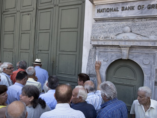 Aposentados tentam sacar seu benefício após bloqueio bancário anunciado pelo governo para evitar a quebra dos bancos (Foto: Petros Giannakouris / AP)