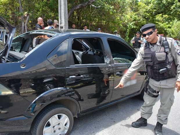 Policial mostra as perfurações de bala no carro que os bandidos usaram para fugir após assalto, em Cabedelo (Foto: Walter Paparazzo/G1)
