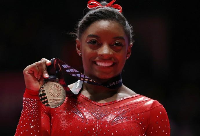 Simone Biles posa com sua medalha após o seu tri mundial no individual geral (Foto: Reuters)