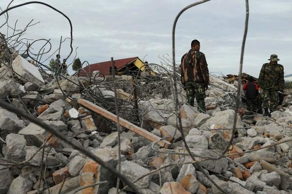 Soldados da equipe de resgate buscam sobreviventes entre os destroços provocados por um terremoto que atingiu o norte da ilha de Sumatra, na Indonésia. Ao menos 27 pessoas morreram e 200 ficaram feridas (Foto: AP Photo/Syahrol Rizal)
