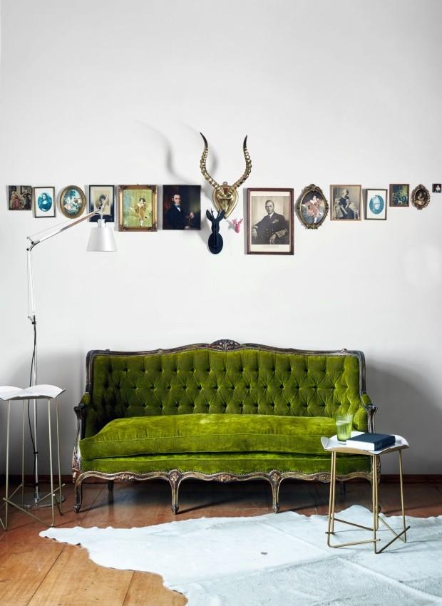 Equilíbrio. No quarto principal, o verde vivo do veludo usado no antigo sofá francês é o grande atrativo. Acima dele, uma organização meticulosa e inesperada de porta-retratos (Foto: Greg Cox / Bureaux)