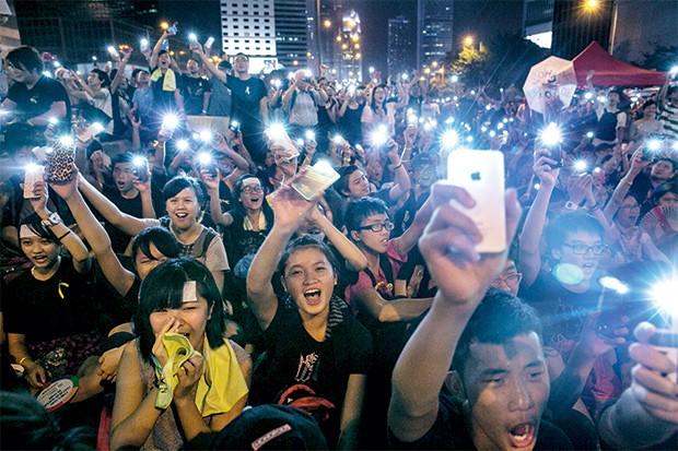 Revolução dos  Guarda-Chuvas | 2014 Em setembro, manifestantes ocuparam o centro de Hong Kong pedindo reforma política. Também queriam evitar que o governo chinês bloqueasse as redes sociais em Hong Kong. O guarda-chuva, usado para a defesa contra os policiais, virou símbolo do movimento. (Foto: Paula Bronstein/ Getty Images)