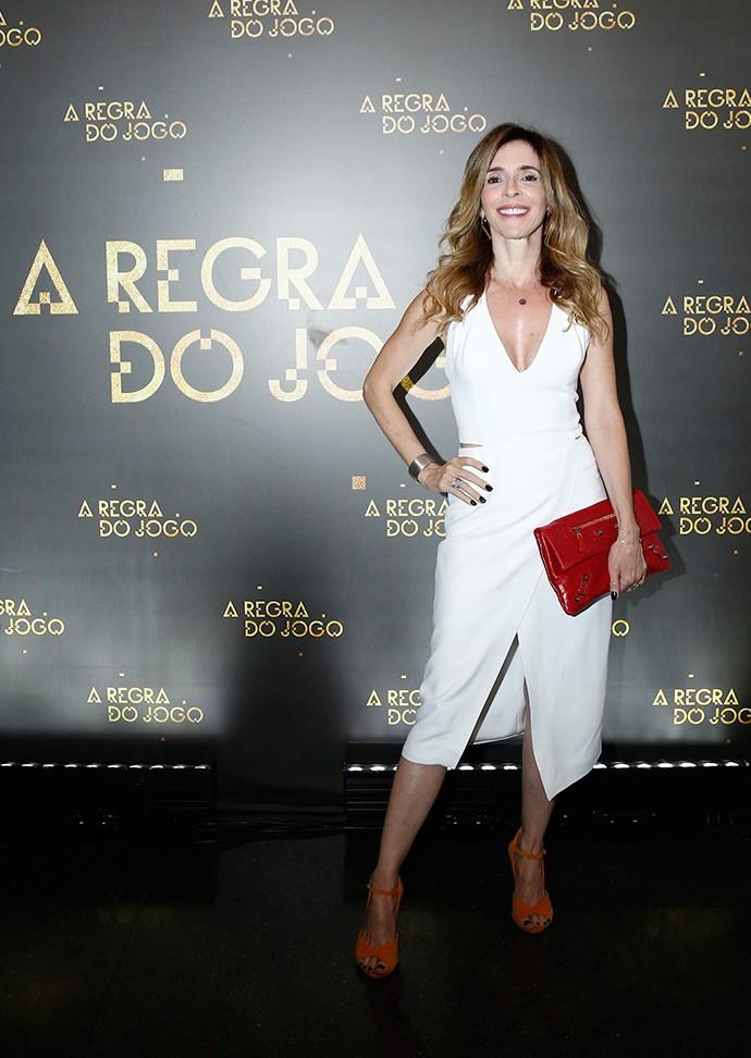 Deborah esbanja elegância em vestido branco com recorte nas laterais; para colorir o visual: sandálias laranjas e bolsa vermelha (Foto: Raphael Dias/Gshow)