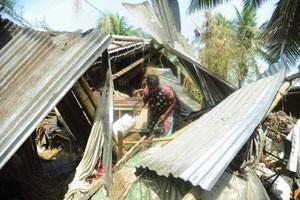 Mulher tenta recuperar parte dos móveis de sua casa que foi destruída por tornado (Foto: Reuters)