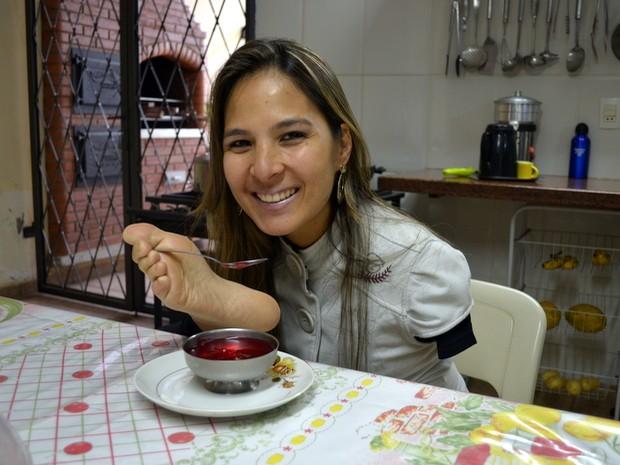 Sem o auxílio de ninguém Carolina utiliza os pés para comer (Foto: Fernanda Zanetti/G1)