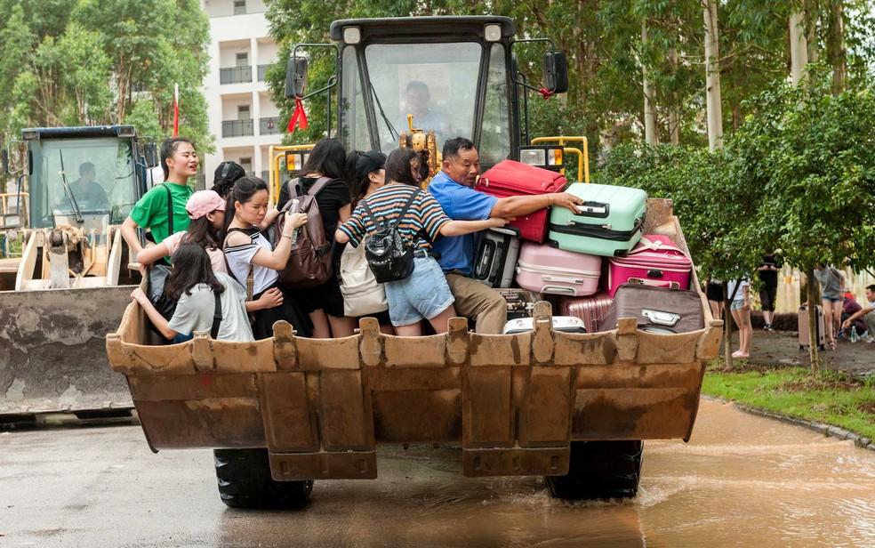 Trator transporta alunos de faculdade em Guilin, na província de Guangxi, através de área inundada (Foto: Reuters)