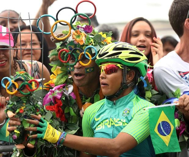 Torcedor leva boneca fantasiada e tira foto com a ciclista Clemilda Fernandes Silva.  (Foto: Bryn Lennon/AP)