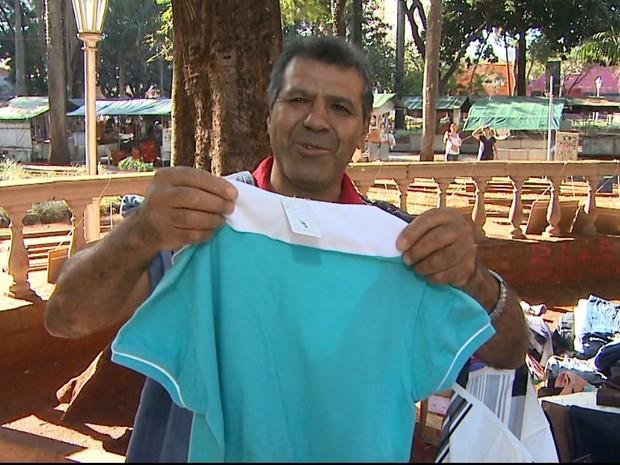 José Lázaro dos Santos mostra camiseta adquirida na loja de rua (Foto: Ronaldo Oliveira/EPTV)