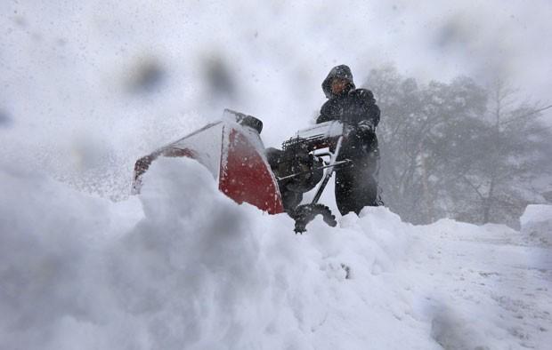 Homem tenta limpar neve acumulada nas ruas de Buffalo, nos Estados Unidos, nesta terça-feira (18) (Foto: The Buffalo News, Harry Scull Jr/AP)