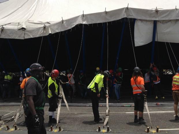 Funcionários erguendo a tenda que tem mais de cem cabos de aço (Foto: Thais Kaniak / G1 PR)