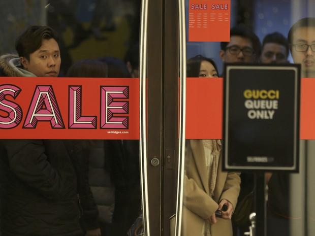Pessoas fazem fila antes de abertura de loja na Inglaterra no Boxing Day (Foto: Neil Hall / Reuters)