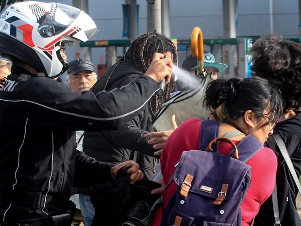 Policial joga spray de pimenta em uma manifestante na rodovia Raposo Tavares, em São Paulo. Funcionários e estudantes da Universidade de São Paulo (USP) fizeram barricadas no local em protesto contra a terceirização e o ajuste fiscal (Foto: Werther Santana/Estadão Conteúdo)