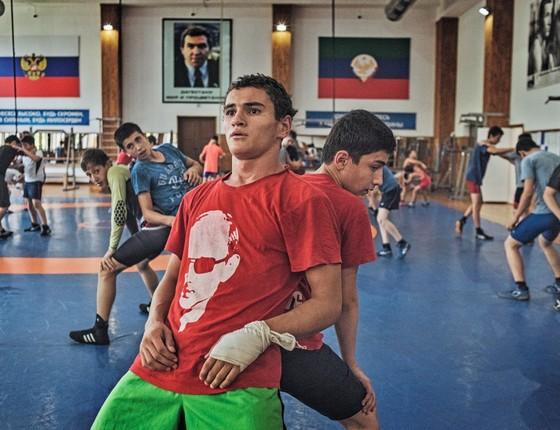 Garotos treinam luta grecoromana na escola Makhachkala,no Daguestão, uma fábrica de campeões. Além de lutar, eles recebem educação moral. A camiseta com o rosto de Putin é comum entre os jovens (Foto: Yuri Kozyrev / NOOR)