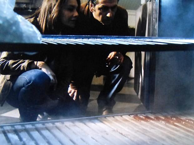 Rosa e Pedroso olham mancha de sangue no freezer da mansão (Foto: O Rebu / TV Globo)