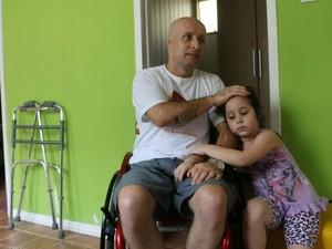 Leandro ao lado da filha Lívia. Ao fundo, o andador usado pelo cadeirante (Foto: Felipe Truda/G1)