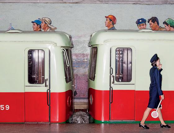 Mulher caminha na plataforma da estação de  metrô Yonggwang, em Pyongyang. O mural e o trem formam um conjunto retrô de anúncio da década de 1950 – em 2017 (Foto: Max Pinckers)
