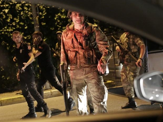 Agentes de segurança da Turquia detem policiais ao lado da estrada, em Istambul (Foto: Yasin Akgul / AFP )