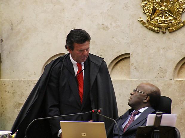 O ministro Luiz Fux (de pé) conversa com o presidente do Supremo, Joaquim Barbosa, durante sessão no plenário do tribunal (Foto: Gervásio Baptista/SCO/STF)