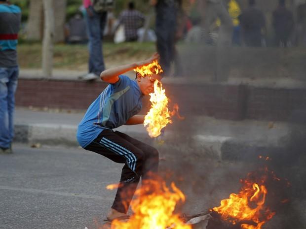 Garoto tenta pegar um pedaço de papel que queima durante confrontos de partidários da Irmandade Mulçumana com a polícia no Cairo. (Foto: Louafi Larbi/Reuters)