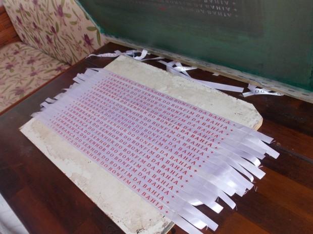 Novas fitas brancas do Bonfim com frase escrita em vermelho  (Foto: Maiana Belo/G1 Bahia)