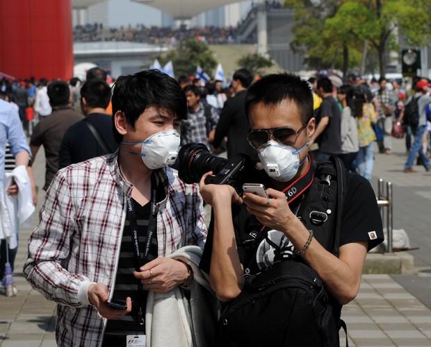 Chineses usam máscaras em Xangai, cidade onde mais duas mortes pelo novo vírus da gripe aviária foram registradas (Foto: Mark Ralston/AFP)