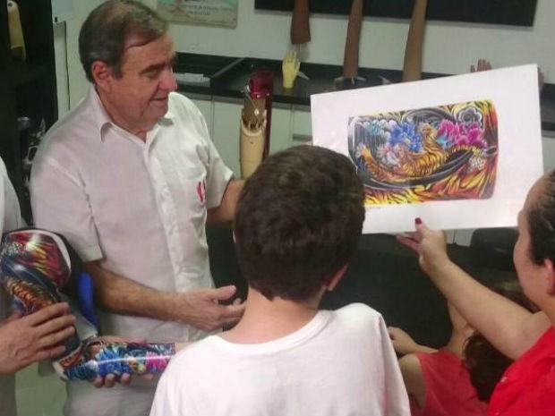 Nolé mostra desenho da prótese para Vrajamany e a mãe (Foto: Ana Carolina Levorato/G1)