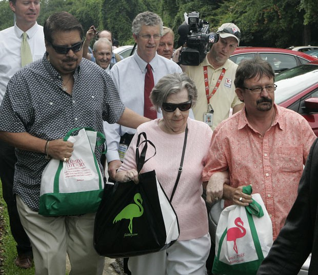 Gloria C. Mackenzie, 84, deixa o escritório da loteria, escoltada por seu filho Scott, à direita, nesta quarta-feira (5), após pegar o cheque em Tallahassee (Foto: Steve Cannon/AP)