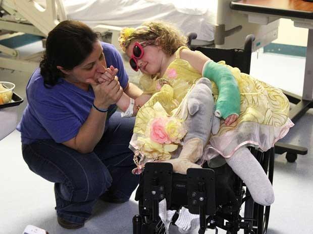 Irlanda Nugent recebe um beijo de sua mãe, Nicole Nugent, na saída do hospital na Flórida (EUA) (Foto: AP Photo / The Tampa Tribune, Andy Jones, Pool)