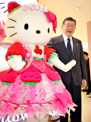 Shintaro Tsuji, presidente da Sanrio, criadora da Hello Kitty, posa ao lado de boneca da personagem (Foto:  AFP PHOTO/FILES/Yoshikazu TSUNO)