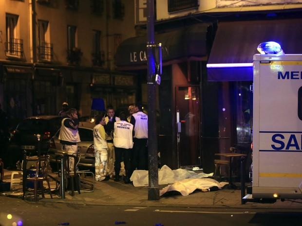 Corpos de vítimas de tiroteio foram cobertos na calçada em frente a um restaurante de Paris, na França (Foto: Philippe Wojazer/Reuters)