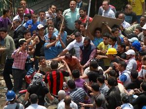 Homem é cercado e agredido durante protestos no Cairo, capital do Egito, nesta quarta-feira (2) (Foto: Reuters)
