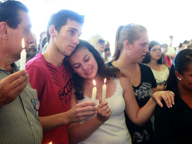 Durante o culto ecumênico, familiares e amigos seguram velas lembrando as 237 vítimas do incêndio na boate Kiss, em Santa Maria. (Foto: Wesley Santos/Estadão Conteúdo)