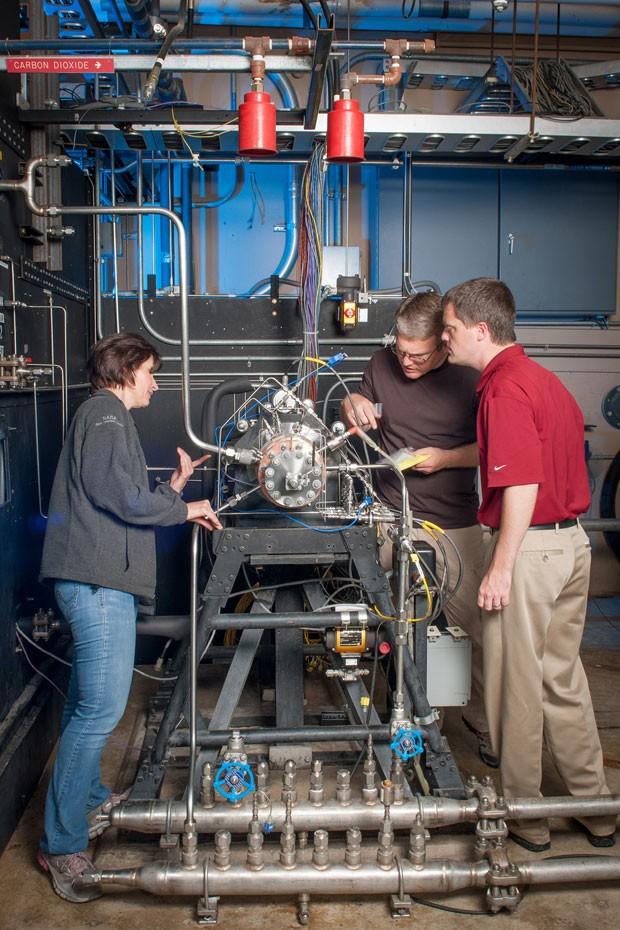 O diretor do projeto Tyler Hickman, de vermelho, e técnicos da Nasa inspecionam o injetor de foguete fabricado por uma impressora 3D (Foto: Divulgação/Nasa)
