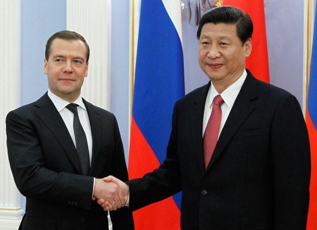 Presidente chinês, Xi Jinping (à direita), com o primeiro-ministro russo, Dmitry Medvedev (Foto: Dmitry Astakhov/AP)