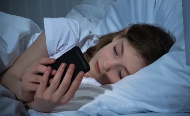 Menina mexendo no celular na cama (Foto: Thinkstock)
