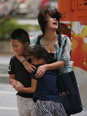 Mãe protege seus filhos da força dos ventos de 'Soudelor' (Foto: Wally Santana / AP Photo)