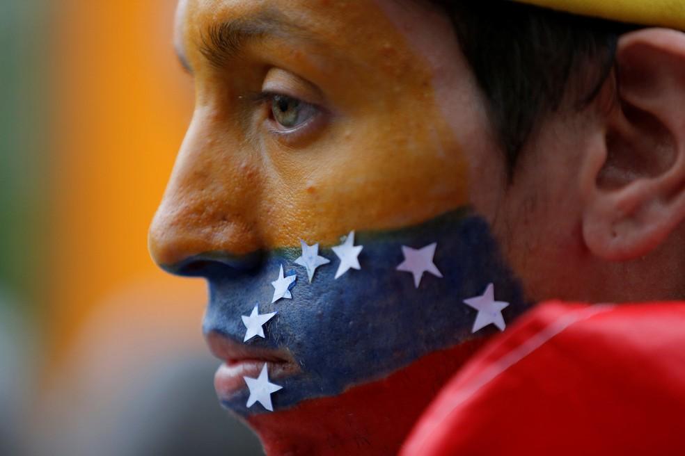 Um homem com o rosto pintado nas cores nacionais da Venezuela assiste a um evento em homenagem ao manifestante Neomar Lander, de 17 anos, que morreu durante confrontos com forças de segurança, em Caracas, na Venezuela (Foto: Ivan Alvarado/Reuters)