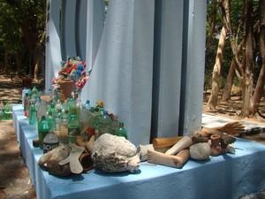 Pessoas deixam garrafas com água e parte de corpo feitas em madeira  (Foto: Gilcilene Araújo/G1)
