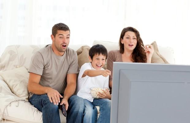 Pais assistindo televisão com os filhos (Foto: ThinkStock)